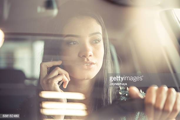 Junge glückliche Frau spricht am Telefon während der Fahrt