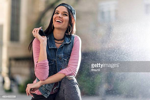 Young happy woman talking to someone over speaker.