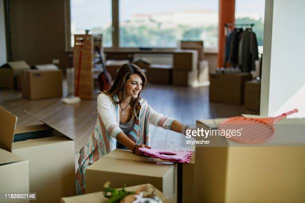 young happy woman unpacking her belongings at new apartment. - one young woman only stock pictures, royalty-free photos & images