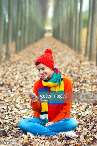 young happy woman using phone in the autumn forest - shawl stock photos and pictures