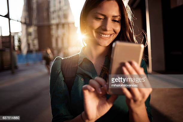 Young happy woman using smartphone
