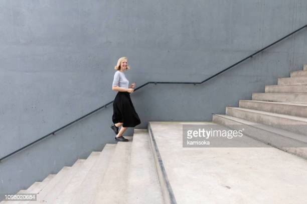 young happy woman walking on stairs by concrete wall - gradino foto e immagini stock