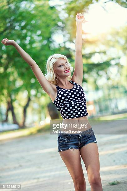 Young Happy Woman Walking with Spread Arms in City Park