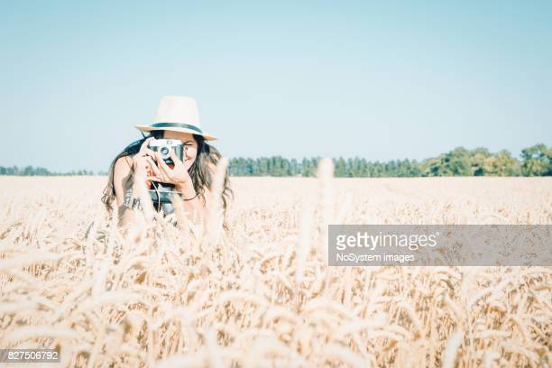 Glückliche Mädchen mit schwarzen langen Haaren, die Spaß im Freien in einem Weizenfeld. Freiheit-Konzept.