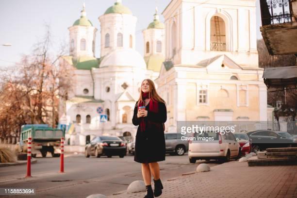 young happy woman with coffee cup walking on sidewalk - kiew stock-fotos und bilder