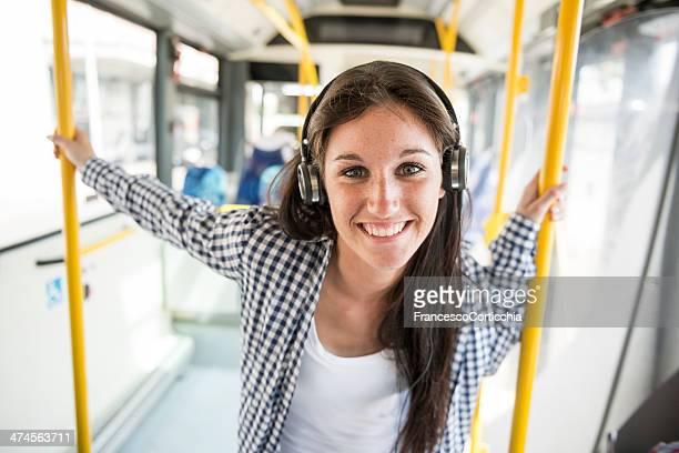 joven mujer feliz con auricular de teléfono en el autobús - bus fotografías e imágenes de stock