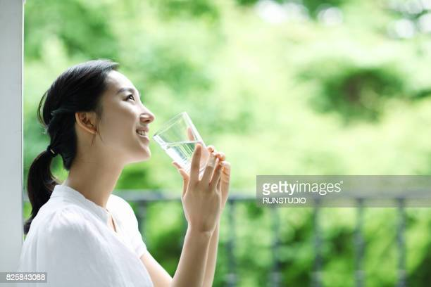 young happy woman with glass of water - asian drink stock photos and pictures