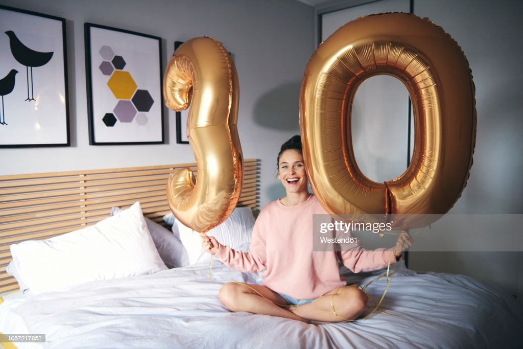 Young happy woman with golden balloons, celebrating her birthday : Stock Photo