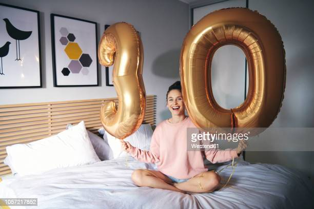 Young happy woman with golden balloons, celebrating her birthday