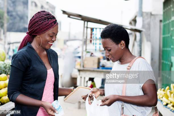 young happy women at the market looking in a bag containing fruit. - abidjan bildbanksfoton och bilder