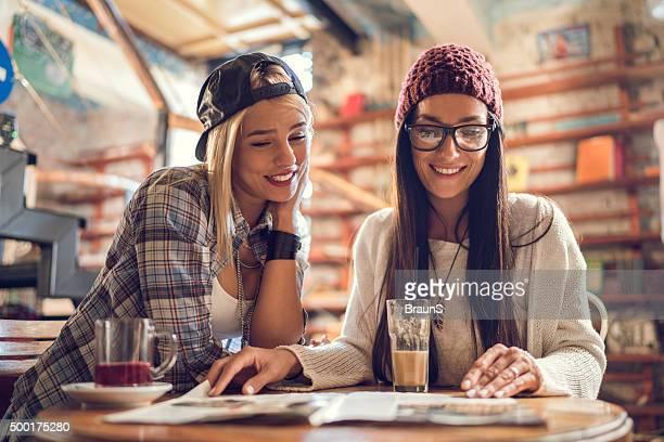 Feliz joven mujer descansando en un café y lee una revista.