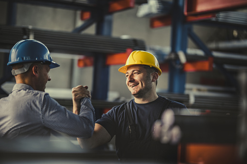 Young happy worker and manager giving each other manly greet at steel mill. 1057484742