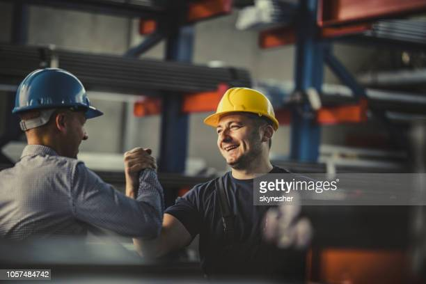 young happy worker and manager giving each other manly greet at steel mill. - built structure stock pictures, royalty-free photos & images