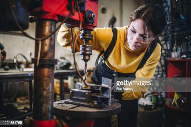 young hard working woman drilling metal - metal industry stock pictures, royalty-free photos & images