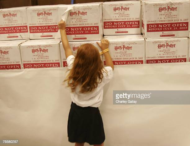 A young Harry Potter fans rips away the wrapping paper to reveal unopened boxes of 'Harry Potter and the Deathly Hallows' books prior to sale at the...