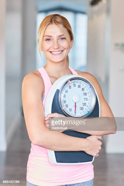 Young healthy girl holding a home scales