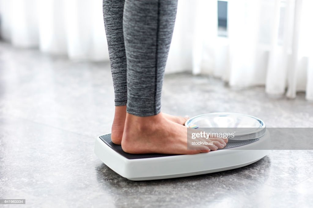 Young healthy girl on home scales : Stock Photo