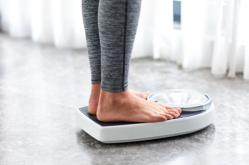 Young healthy girl on home scales 641963334