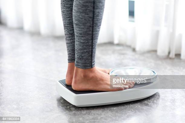 young healthy girl on home scales - beautiful female feet stock photos and pictures