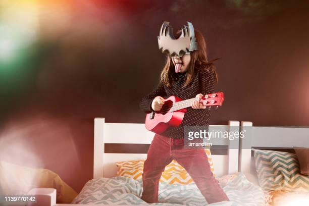 young heavy metal fan girl having a virtual reality immersion playing an ukulele - heavy metal stock pictures, royalty-free photos & images