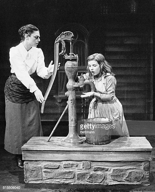 Young Helen Keller and her teacher Anne Sullivan go to fill a bucket at the water pump during a performance of the William Gibson Broadway play 'The...