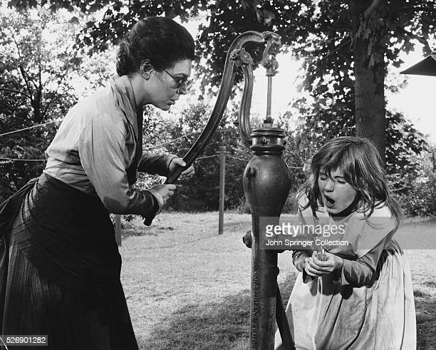 Young Helen Keller and her teacher Anne Sullivan go to fill a bucket at the water pump As the water pours over her hand Helen suddenly realizes what...