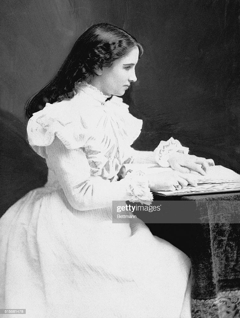 Helen Keller Sitting at a Desk : News Photo