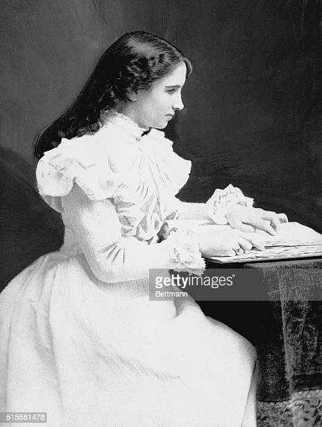 Young Helen Keller sits with a book at her desk Due to illness Keller suffered loss of sight and hearing at the age of 19 months