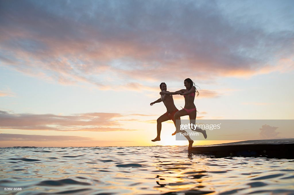 Young heterosexual couple jumping into water at sunset : Stockfoto
