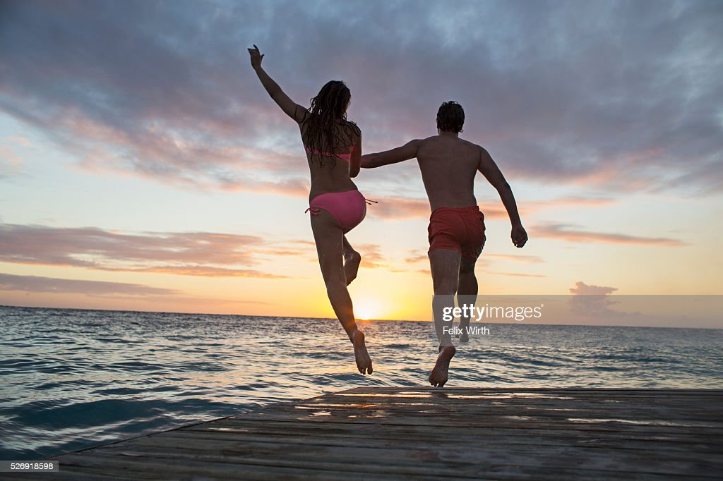 Young heterosexual couple jumping into water at sunset : Stock-Foto
