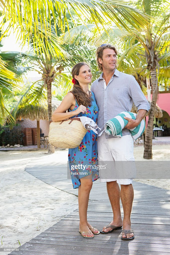 Young heterosexual couple standing on beach : Photo
