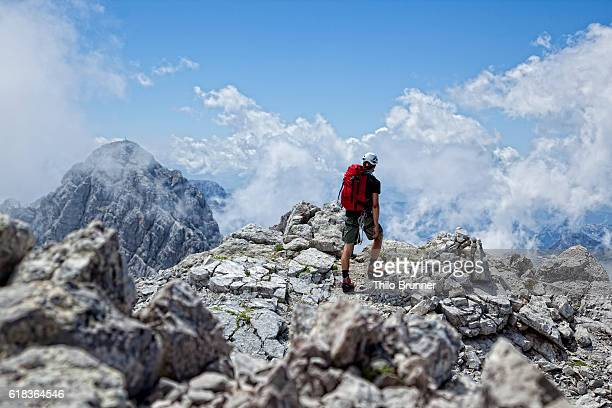 Young hiker contemplating high mountain landscape