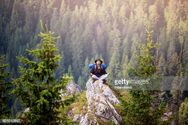 young hiker doing yoga on mountain - meditieren stock-fotos und bilder
