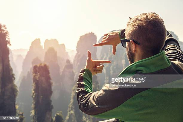 Young hiker male framing landscape with fingers