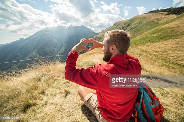 Young hiker man making heart shape loving the nature