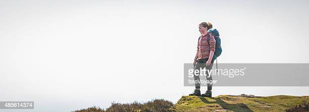 Young hiker on mountain top looking out over view panorama