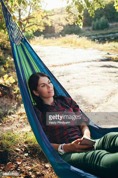 Young hiker resting on hammock in forest