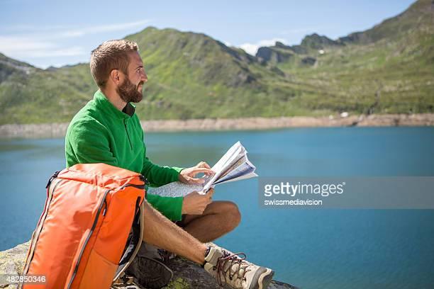 Junge Wanderer suchen am rock Wanderwege auf der Karte