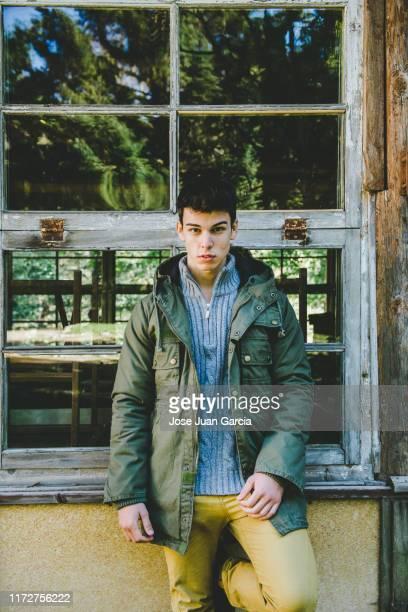joven excursionista esperando frente a una cabaña rústica en el bosque - turismo ecológico fotografías e imágenes de stock