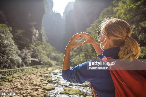 Young hiker woman framing landscape in love frame