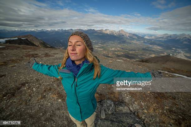 Young hiker woman standing on a mountain top arms outstretched