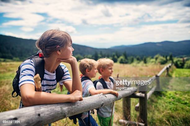 Young hikers leaning on a wooden fence in the Gorce Mountains