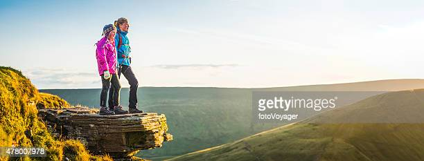Young hikers on mountain top overlooking golden sunlight landscape panorama