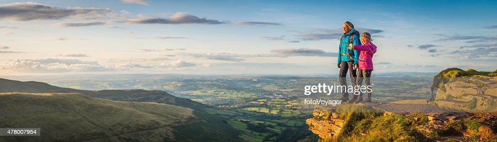 Jeunes randonneurs au sommet de la montagne surplombant un paysage idyllique panorama du coucher de soleil : Photo