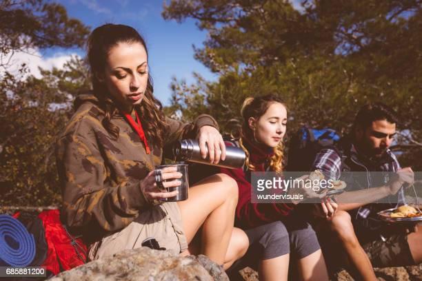 休憩と食事を森の中の若いハイカー