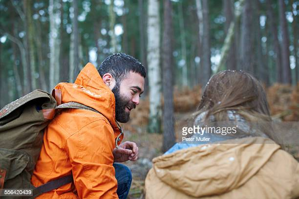 Young hiking couple crouching in forest