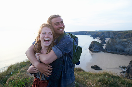 Young hiking couple embracing and laughing on Atlantic coastline. - gettyimageskorea