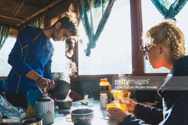 Young hiking couple enjoy breakfast in mountain hut