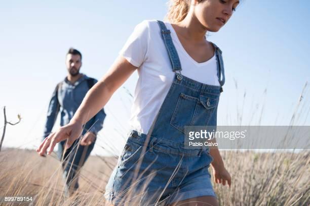 Young hiking couple hiking through long grass, Las Palmas, Canary Islands, Spain