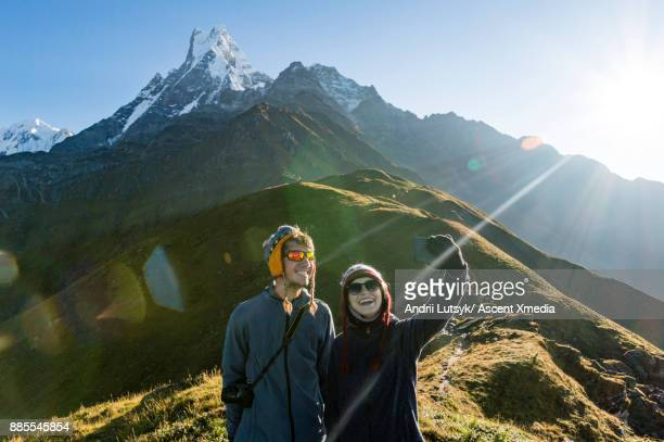 Young hiking couple take smart phone selfie, in mountains